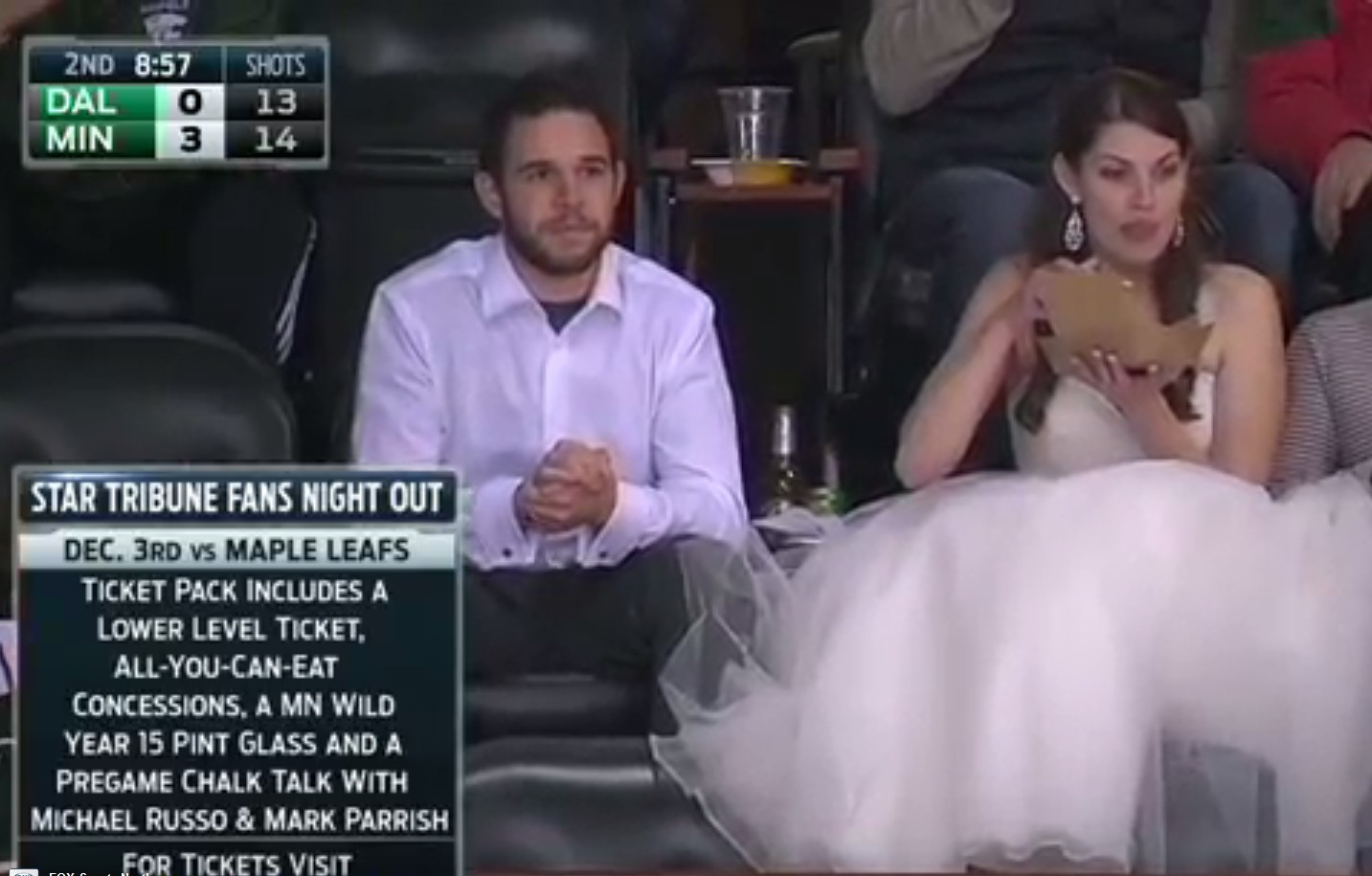Relationship Goals: Woman wears wedding dress at hockey game
